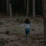 A girl runs into the forest