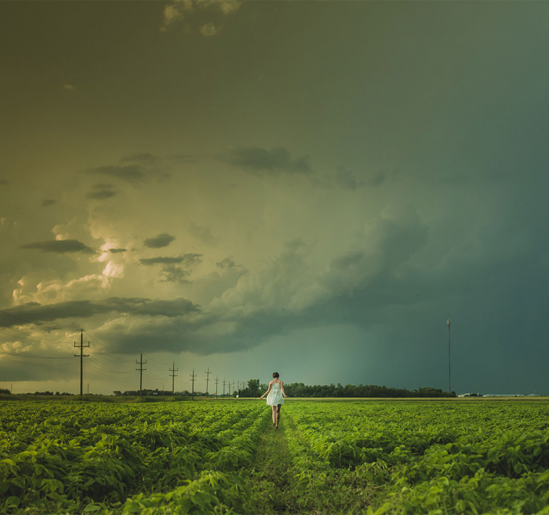 A in a woman in a white dress runs in a green field with storm clouds overhead