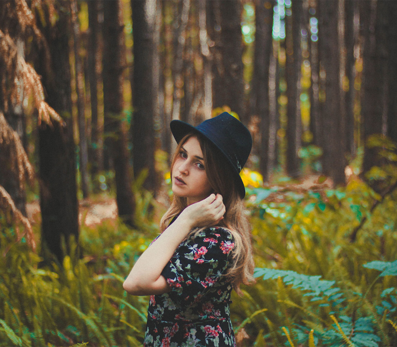 A teenage girl stands in a forest in a black hat and floral dress